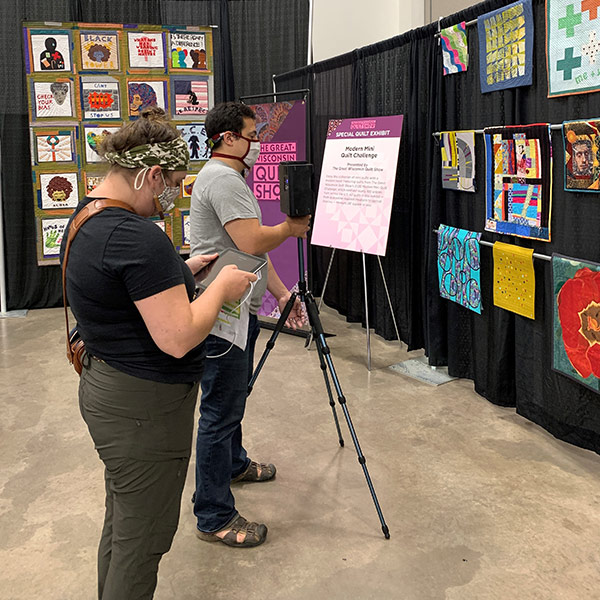 Two people taking photos at a quilt exhibit